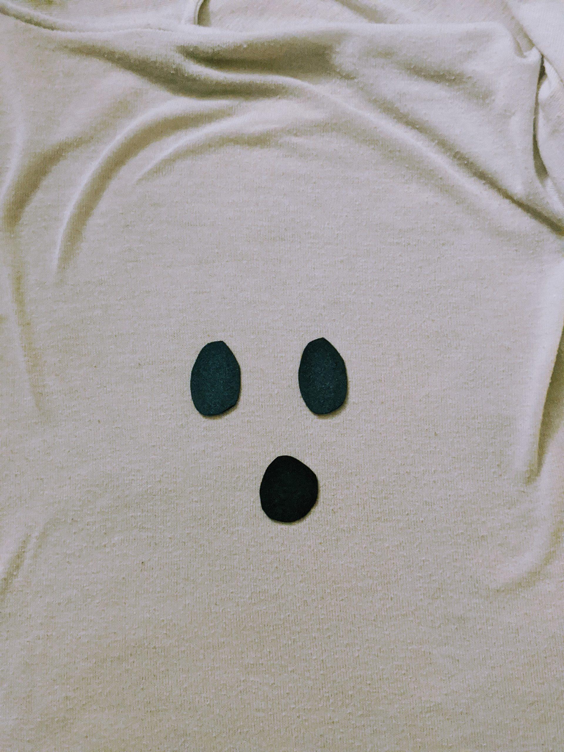 Taping ghost eyes on white sheet