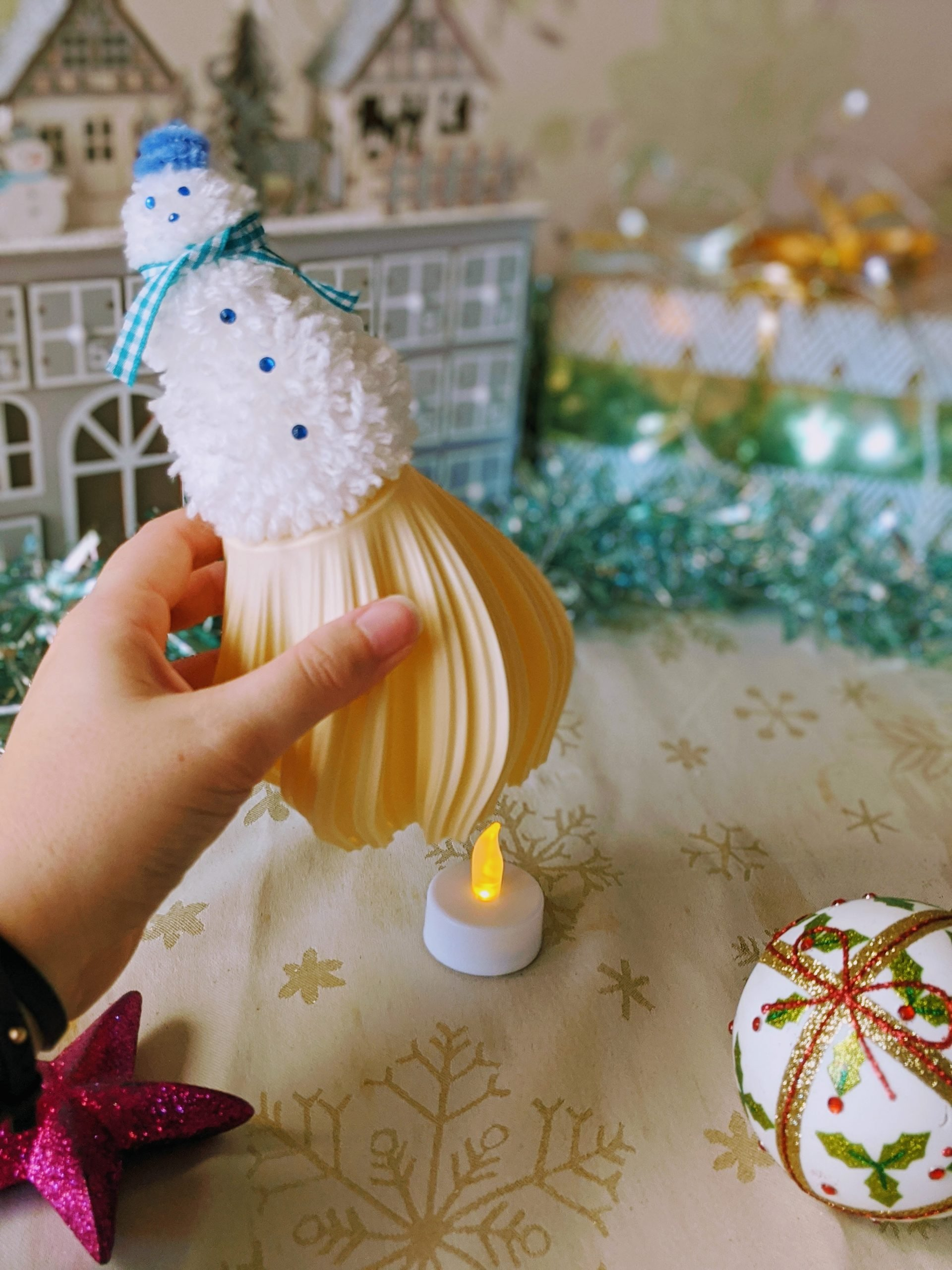 Flameless candle under pom pom snowman ornament